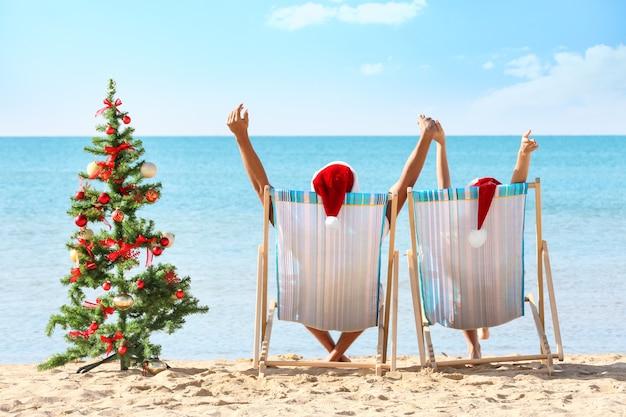 Junges paar und weihnachtsbaum am strand