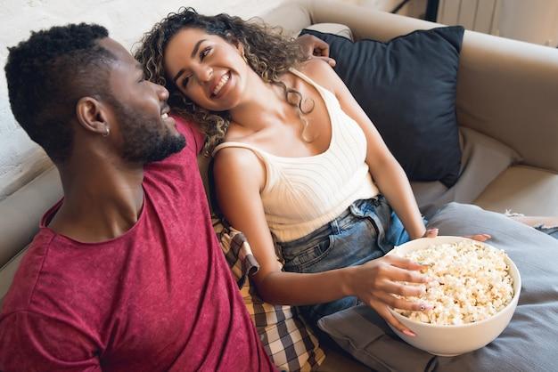 Junges paar verbringt zeit zusammen und schaut sich fernsehserien oder filme an, während es zu hause auf der couch sitzt.