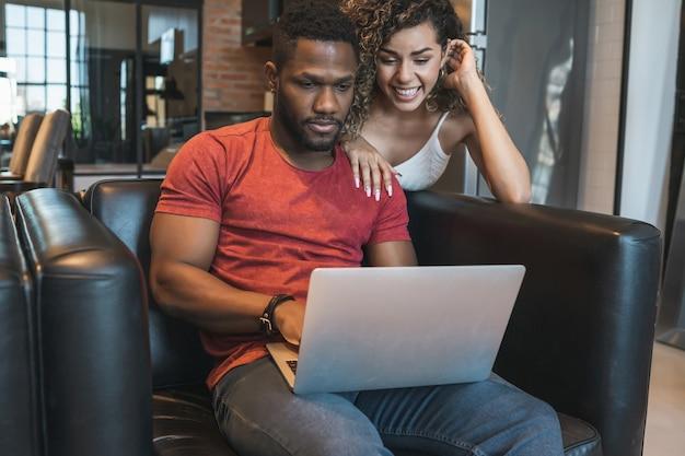 Junges paar verbringt zeit zusammen, während es zu hause einen laptop benutzt.