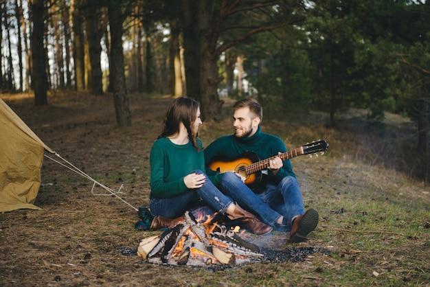 Junges paar verliebt camping-touristen, die am lagerfeuer gegen ein zelt im wald sitzen, das gitarre spielt