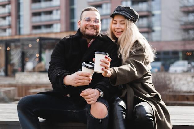 Junges paar verliebt im freien. reisende mit einer tasse kaffee gehen im spring park spazieren. schöner sonniger tag. ein junges paar trinkt kaffee zum mitnehmen