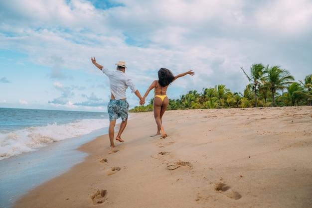 Junges paar verliebt in den strand, sommerferien, glückliches und lächelndes händchenhalten