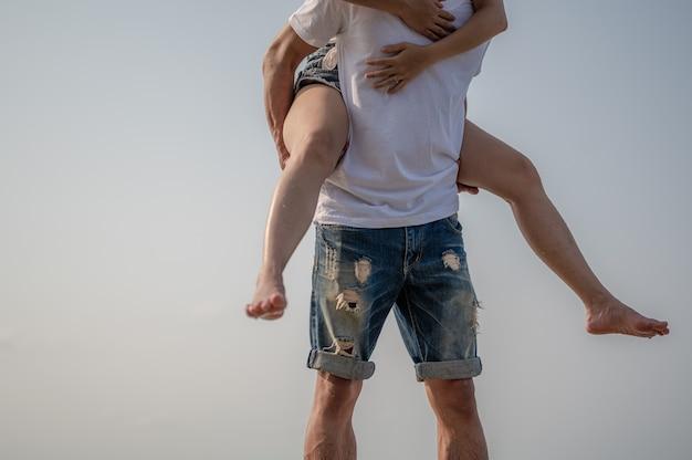 Junges paar verliebt in strand-sommerferien fröhliches mädchen auf jungem freund, der spaß hat