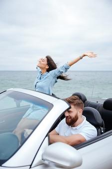 Junges paar verliebt in straßenfahrt, die im cabrioauto fährt