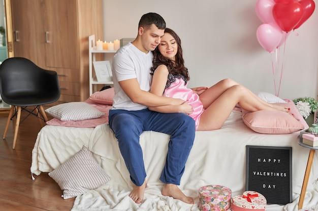 Junges paar verliebt in zu hause auf bett, das valentinstag feiert