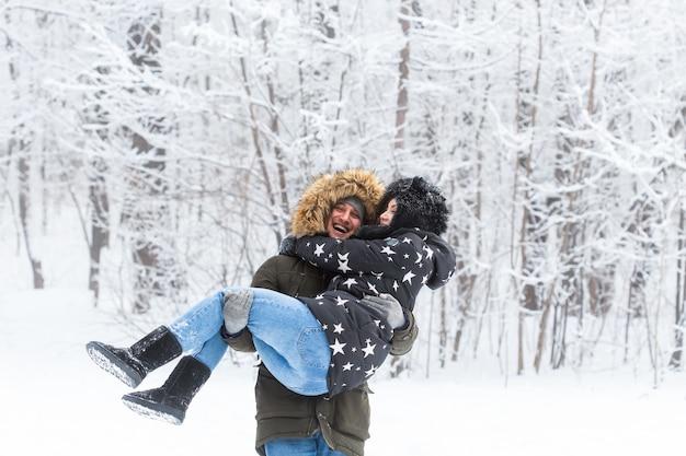 Junges paar viel spaß in einem verschneiten park. wintersaison.