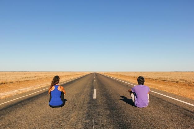 Junges paar von hinten sitzt auf einer endlosen geraden, leeren straße mitten im nirgendwo im australischen outback. backpacker, visionäre, unternehmer, abenteuerkonzepte