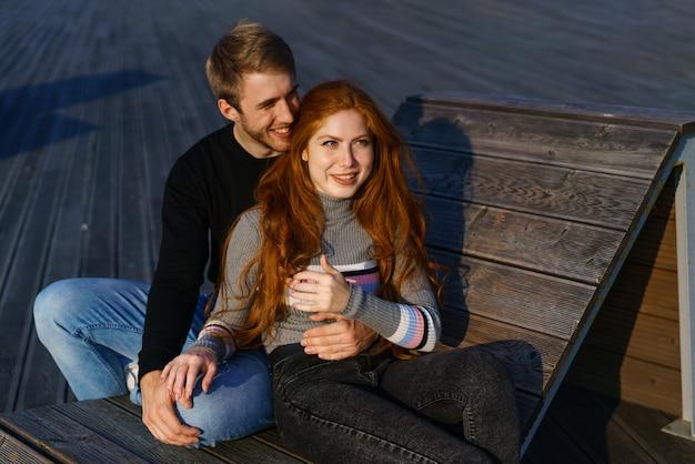 Junges paar von mann und mädchen mit roten haaren von kaukasischem aussehen in freizeitkleidung an einem sonnigen tag, der im park auf einer holzbank in einer glücklichen beziehung zwischen einem mann und einer frau sitzt