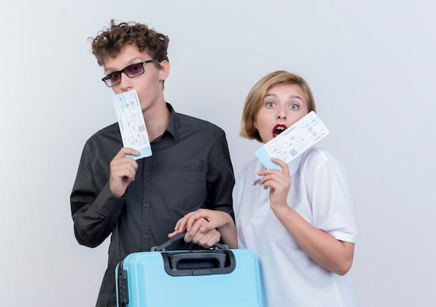 Junges paar von touristen mann und frau, die flugtickets und koffer halten, die erstaunt und überrascht über weißer wand stehen
