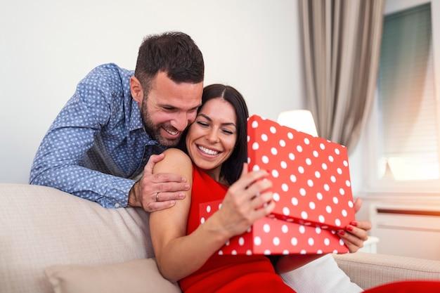 Junges paar zu hause hält ein geschenk. mann überrascht seine frau mit geschenkbox am valentinstag.