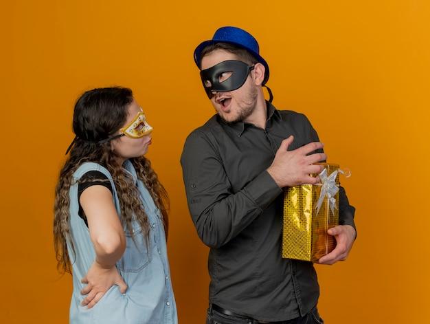 Junges parteipaar, das maskerade-augenmaske trägt, schaut einander kerl an, der geschenk lokalisiert auf orange hält
