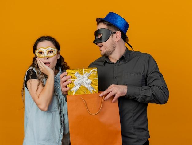 Junges parteipaar, das maskerade-augenmasken-kerl trägt, gab geschenk an überraschtem mädchen lokalisiert auf orange