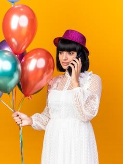 Junges partymädchen mit partyhut, das luftballons hält und am telefon spricht und die seite isoliert auf oranger wand betrachtet