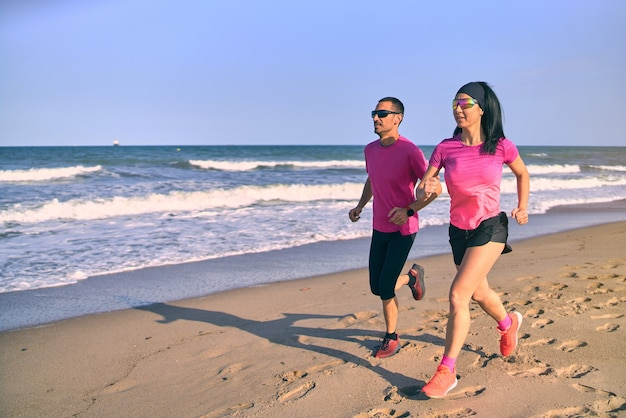 Junges passendes paar, das bei sonnenaufgang am strand läuft. gesunder start in den tag. tragen von rosa und schwarzer sportkleidung. laufen am meer.