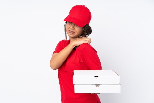 Junges pizzabotenmädchen über weiß, das unter schulterschmerzen leidet, weil es sich mühe gegeben hat