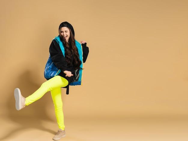 Junges positives mädchen in gelben leggings und einer warmen weste macht einen schritt mit ihrem fuß auf einem pastellorange.