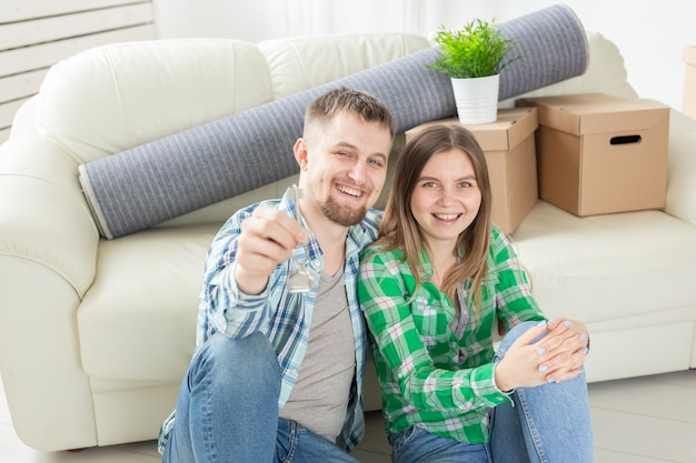 Junges positives paar, das schlüssel zu einer neuen wohnung hält, während sie in ihrem wohnzimmer stehen. einweihungsparty und familienhypothekenkonzept.