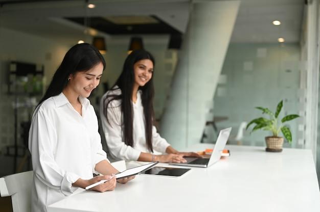 Junges professionelles grafikdesignerteam, das die konzepte zusammen mit laptop und tablet im büro bespricht.