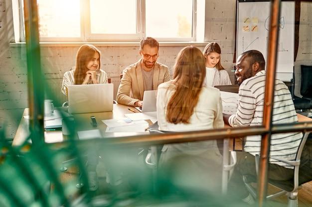 Junges professionelles team. gruppe junger moderner menschen in eleganter freizeitkleidung brainstorming beim sitzen hinter glaswand im kreativbüro