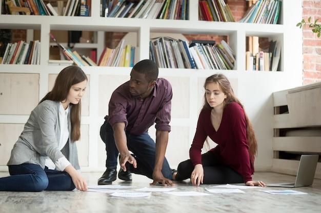 Junges projektteam-brainstorming, das zusammen an büroboden, teamwork arbeitet