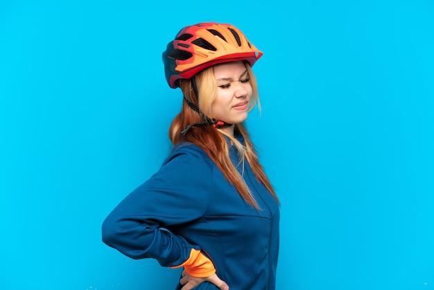 Junges radfahrermädchen isoliert auf blauem hintergrund, das an rückenschmerzen leidet, weil es sich angestrengt hat