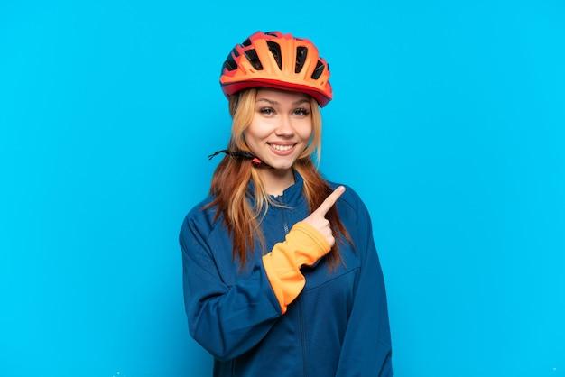 Junges radfahrermädchen isoliert auf blauem hintergrund, das auf die seite zeigt, um ein produkt zu präsentieren