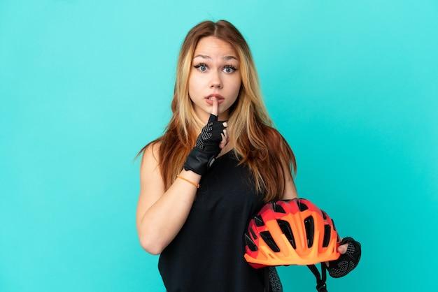 Junges radfahrermädchen über isoliertem blauem hintergrund, das ein zeichen der stille zeigt, geste, die finger in den mund steckt