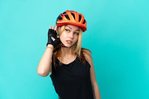 Junges radfahrermädchen über isoliertem blauem hintergrund, das etwas hört, indem es die hand auf das ohr legt