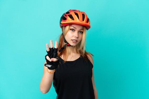 Junges radfahrermädchen über isoliertem blauem hintergrund glücklich und zählt drei mit den fingern