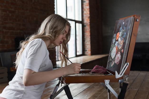 Junges recht blondes mädchen mit der bürste und palette, die nahe gestellzeichnungsbild in einem studio sitzen