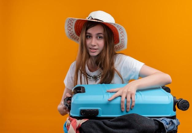Junges reisendes mädchen, das hut hält, der koffer voller tücher hält, der auf isolierte orange wand mit kopienraum schaut