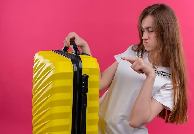 Junges reisendes mädchen, das koffer auf isolierter rosa wand hält