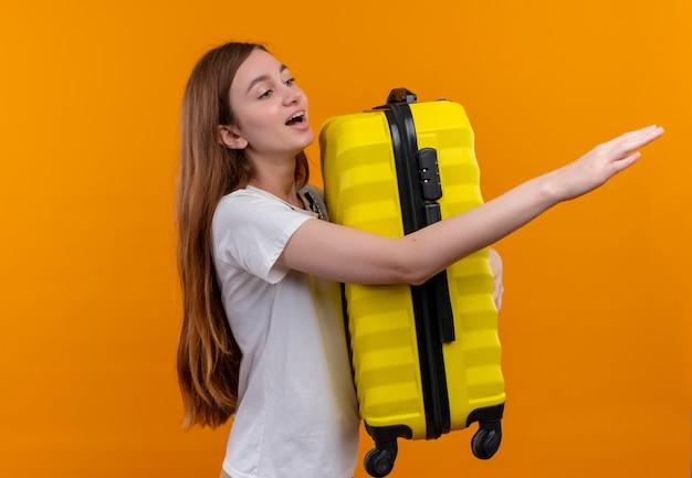 Junges reisendes mädchen, das koffer hält, das hand streckt und rechte seite auf isolierter orange wand mit kopienraum betrachtet