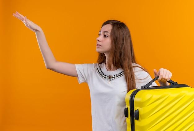Junges reisendes mädchen, das koffer hält und hand an der linken seite auf isolierter orange wand anhebt
