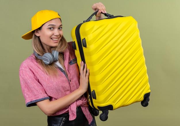 Junges reisendes mädchen, das rosa hemd in der kappe mit kopfhörern um hals hält, hält koffer, der positiv und glücklich bereit zu reisen lächelt