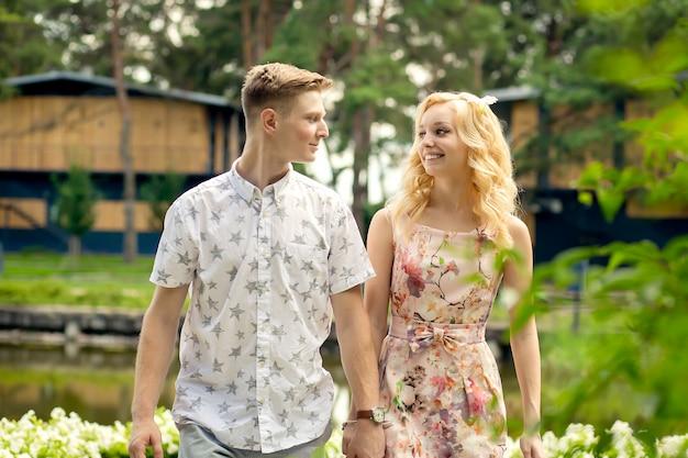 Junges reizend blondes mädchen flirtet und mit einem kerl im garten. liebesgeschichte eines verliebten paares.