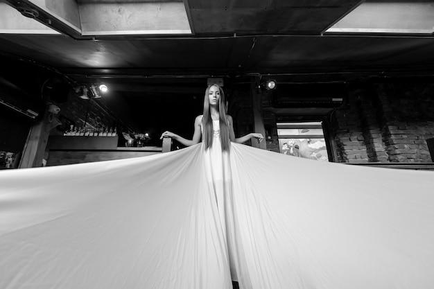 Junges romantisches elegantes mädchen im langen weißen fließenden fliegenden kleid, das auf der treppe innen aufwirft