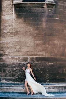 Junges romantisches elegantes mädchen im langen weißen fließenden kleid, das über alte steinmauer aufwirft