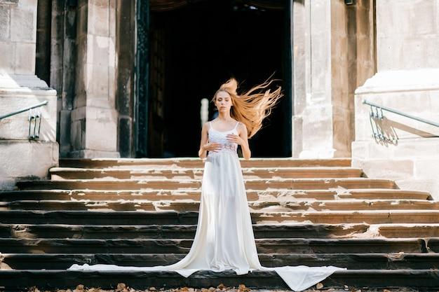 Junges romantisches elegantes mädchen mit fliegenden haaren im langen weißen kleid, das auf der treppe des alten palastes aufwirft