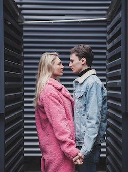 Junges romantisches paar, das hände in der stadt hält