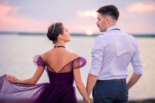 Junges romantisches paar, das sich am strand entspannt und den sonnenuntergang beobachtet