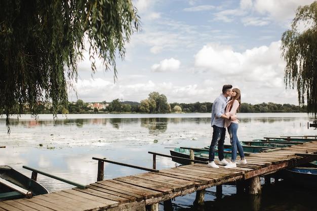 Junges romantisches paar hat spaß am sonnigen tag des sommers nahe dem see. gemeinsam urlaub machen. mann und frau umarmen und küssen sich.