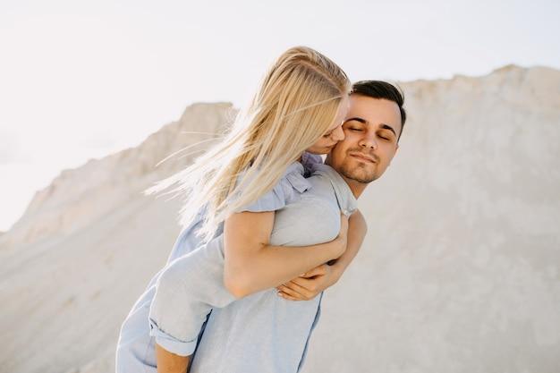 Junges romantisches paar im freien. mann, der der frau ein huckepack gibt, während sie ihn auf die wange küsst.