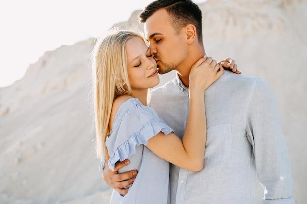 Junges romantisches paar im freien. mann, der frau umarmt und sie auf wange küsst.