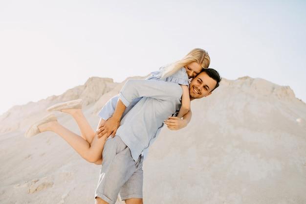 Junges romantisches paar im freien. mann gibt ein huckepackreiten, beide lachen.
