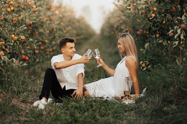 Junges romantisches paar in einem apfelgarten, das auf einer picknickdecke sitzt und einander schaut und gläser mit weißwein anstößt.