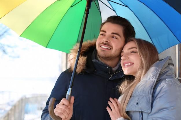 Junges romantisches paar mit buntem regenschirm im freien