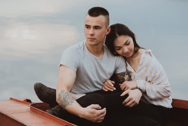 Junges romantisches verliebtes paar, das in einem boot am wasser am sommerabend sitzt