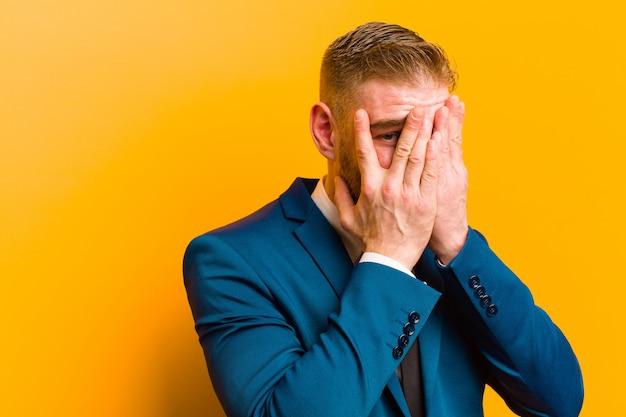 Junges rotes hauptgeschäftsmann-bedeckungsgesicht mit den händen, spähend zwischen finger mit überraschtem ausdruck und schauen zur seite gegen orange