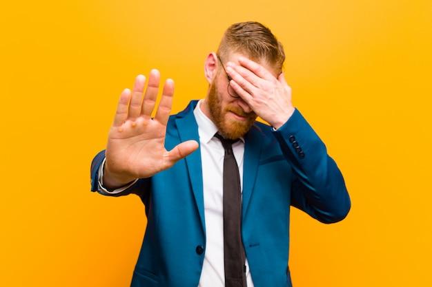 Junges rotes hauptgeschäftsmann-bedeckungsgesicht mit der hand und andere hand voran setzen, um die kamera zu stoppen und fotos oder bilder gegen orange ablehnen